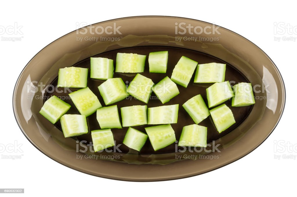 Slices of cucumbers in brown dish isolated on white stock photo