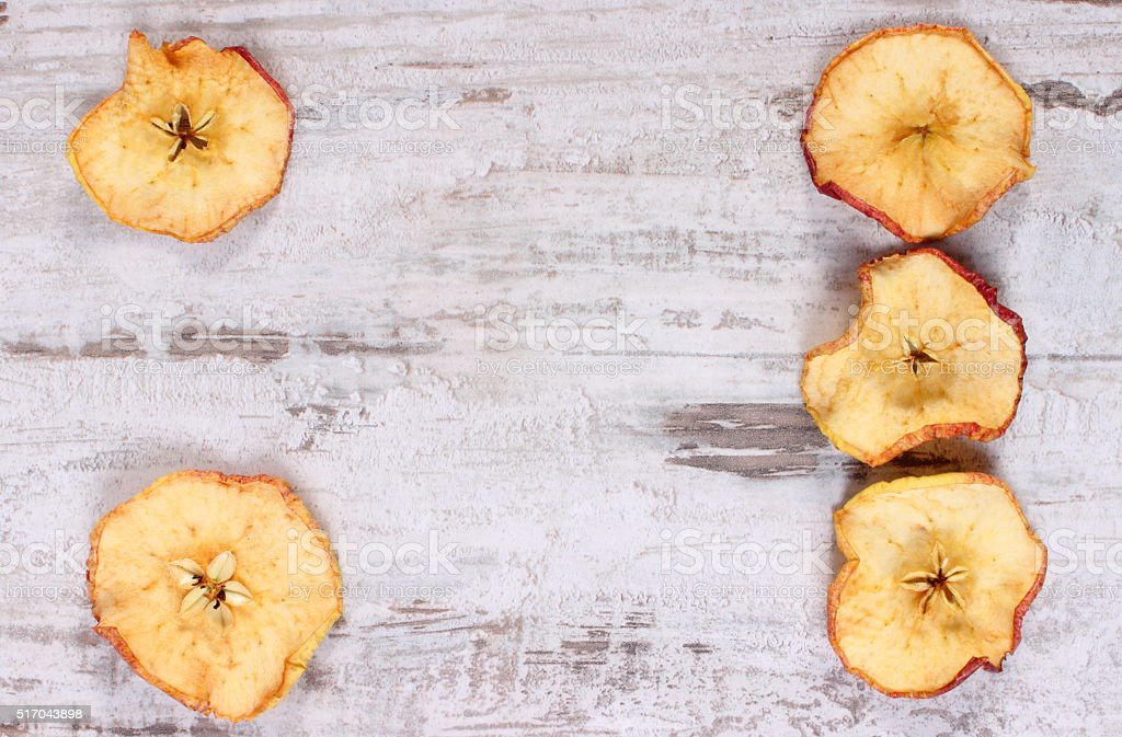 Slices of dried apple on old wooden background stock photo