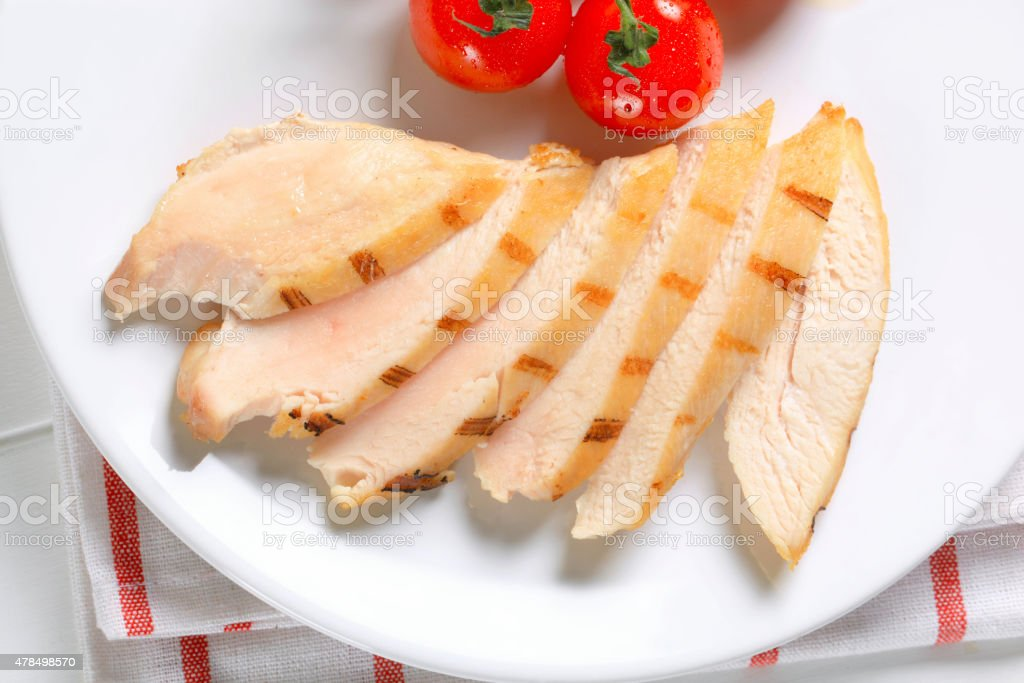 Slices of grilled chicken breast stock photo