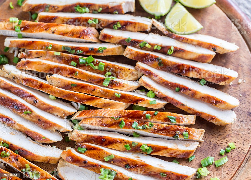 Slices of grilled chicken in lime sauce stock photo