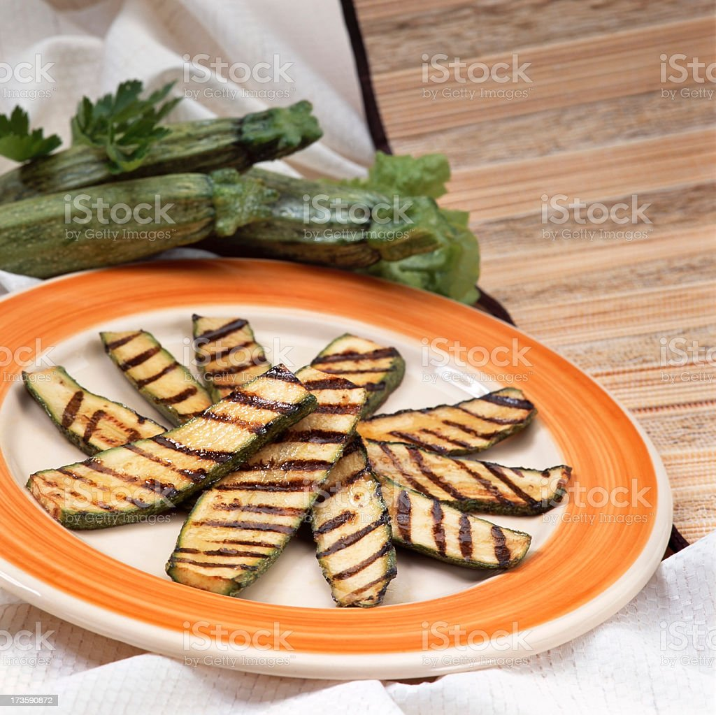 Slices of grilled zucchini on an orange and white plate royalty-free stock photo