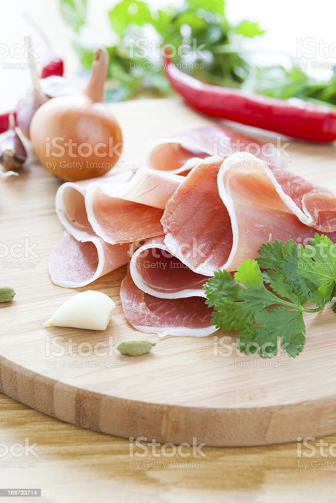 slices of ham on a round wooden board royalty-free stock photo