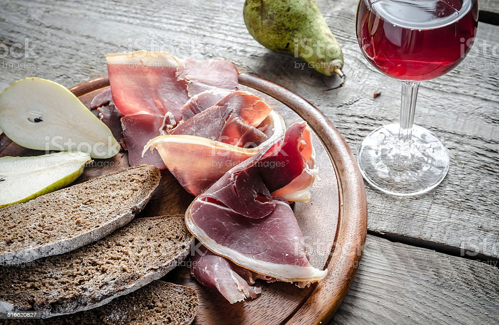 Slices of italian ham on the wooden board stock photo