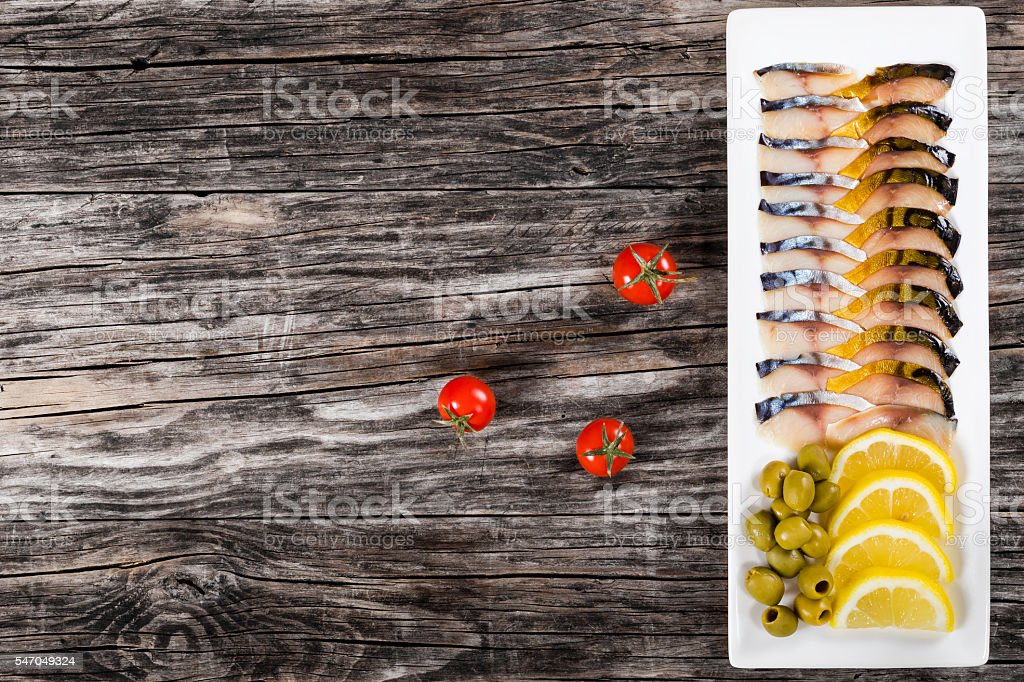 slices of mackerel with lemon, olives and dill, top view stock photo