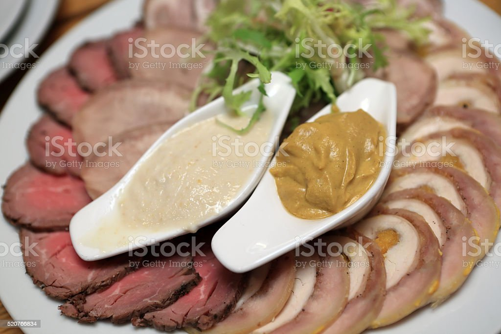 Slices of meat with mustard stock photo