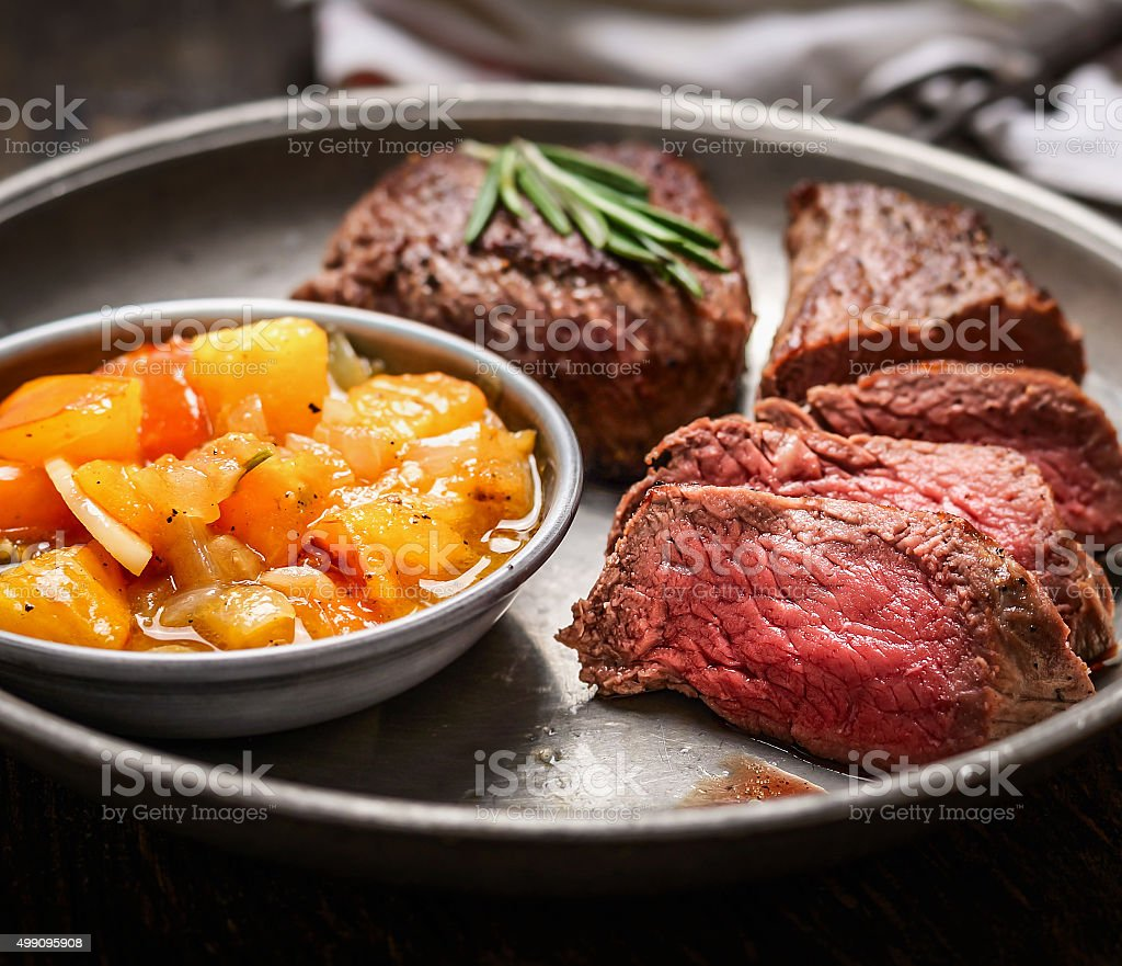 Slices of medium rare roasted meat steak and salsa sauce stock photo