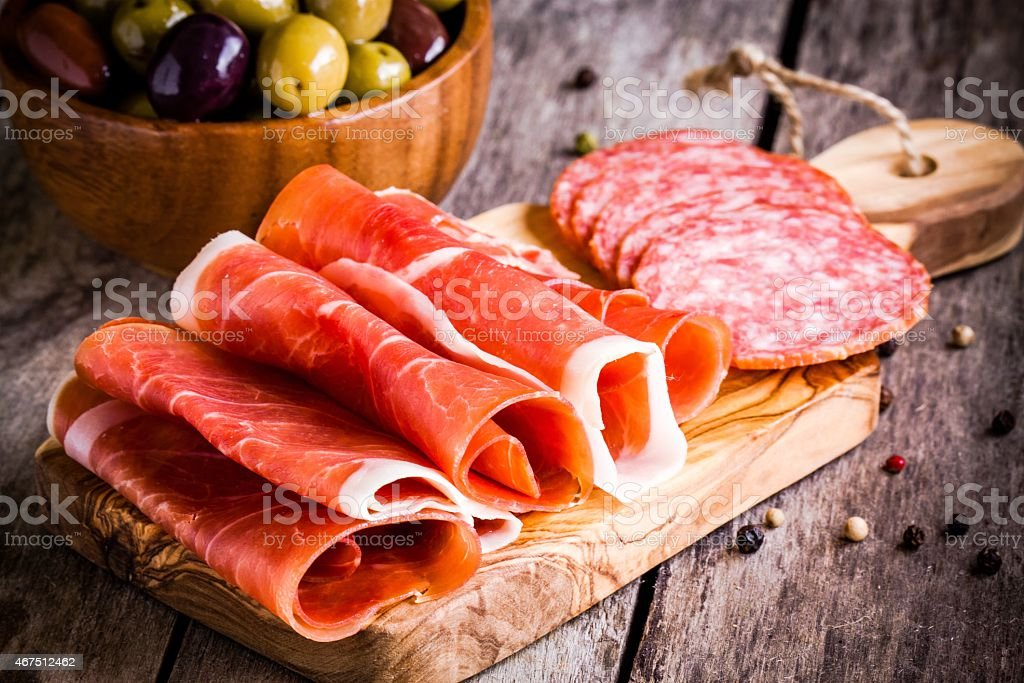 slices of prosciutto with salami and olives on cutting board stock photo