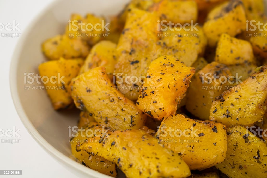 Slices of pumpkin baked with Provencal herbs in vegetable oil royalty-free stock photo