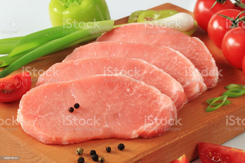 Slices of raw pork steaks on a wooden board with pepper pods stock photo