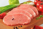 Slices of raw pork steaks on a wooden board with pepper pods