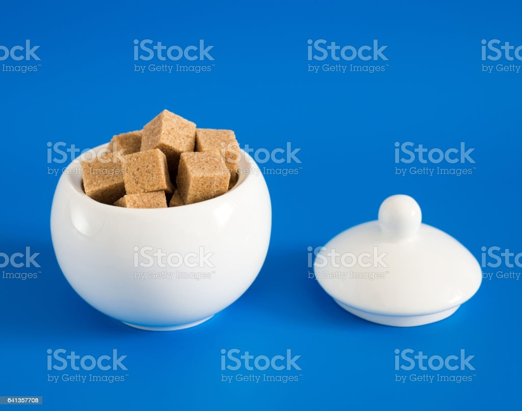 Slices of raw sugar in sugar bowl on blue background stock photo