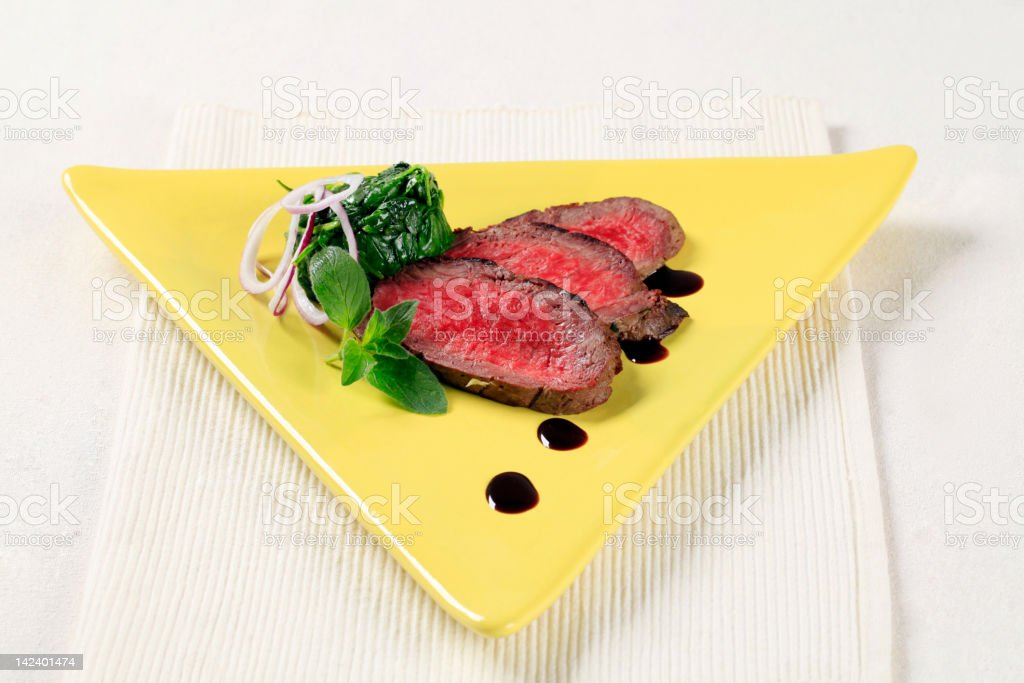 Slices of roast beef and spinach leaves royalty-free stock photo
