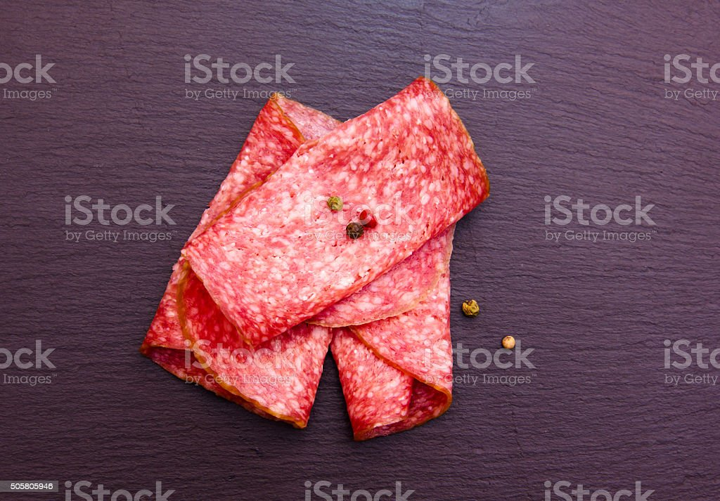Slices of salami on top slate stock photo