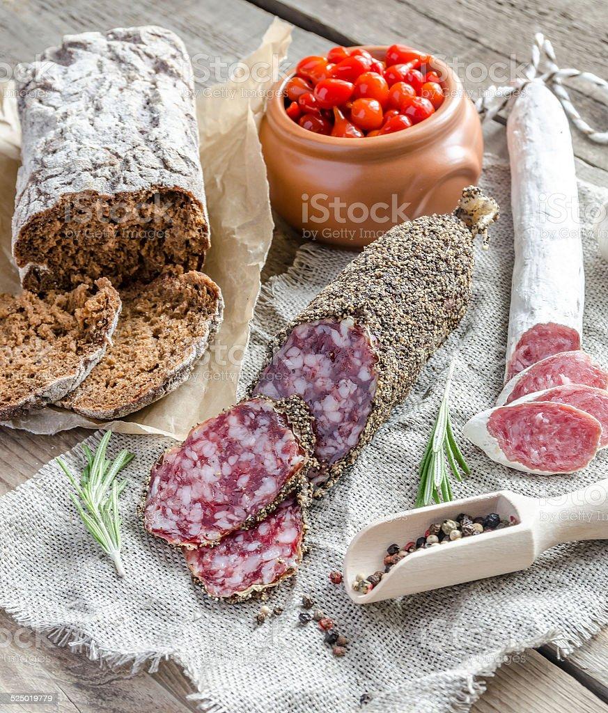 Slices of saucisson and spanish salami on the sackcloth stock photo