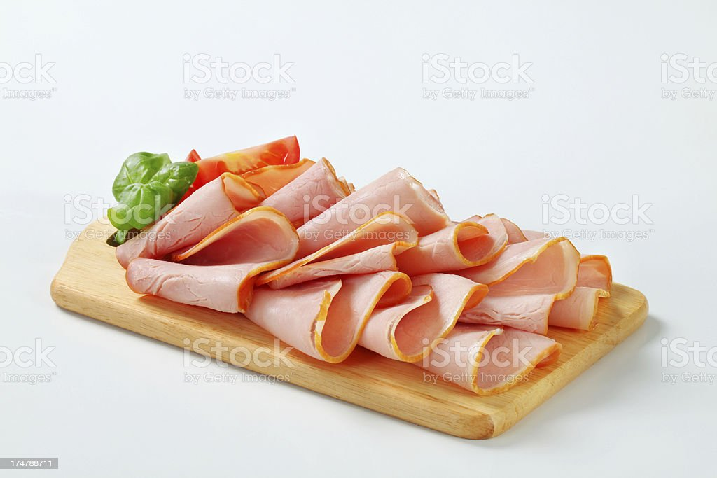 Slices of smoked ham on a cutting board royalty-free stock photo