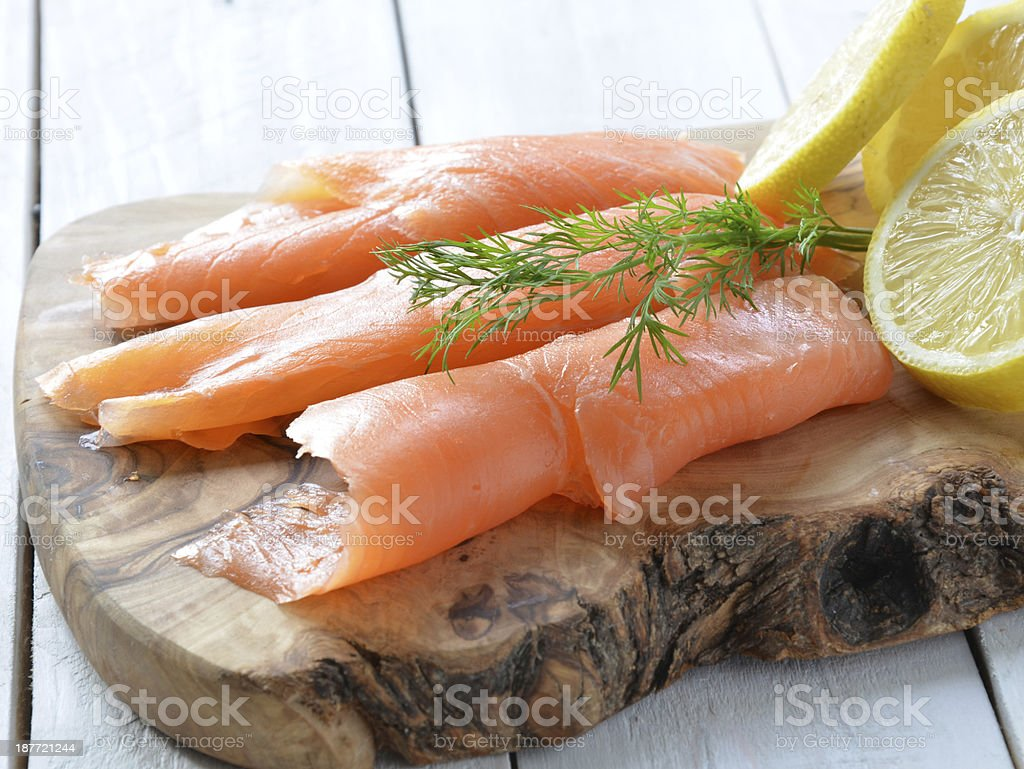 Slices of smoked salmon and fresh lemon on wooden board royalty-free stock photo