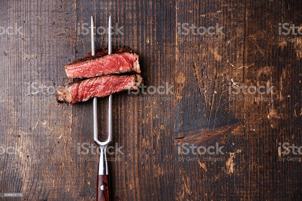 Slices of Steak Ribeye on meat fork stock photo