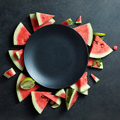 slices of watermelon placed in a circle on black plate