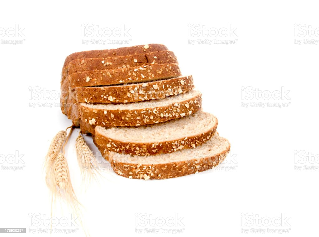 Slices of whole wheat bread on top of wheat grains stock photo