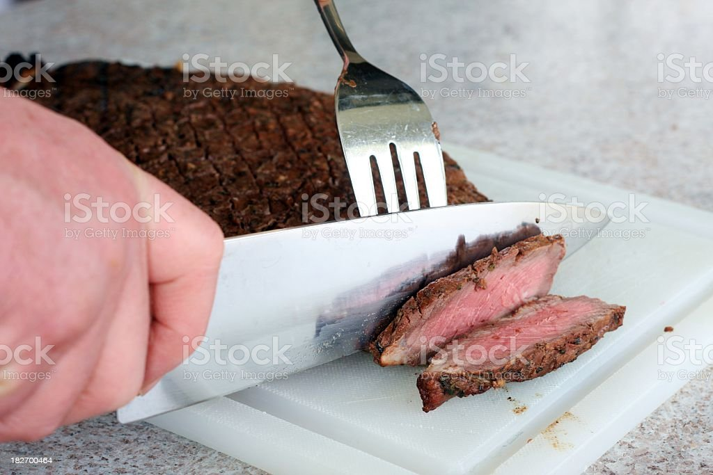 Slicing A London Broil royalty-free stock photo