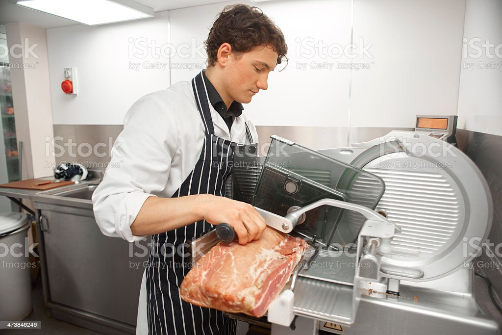 slicing bacon in a butcher's shop stock photo