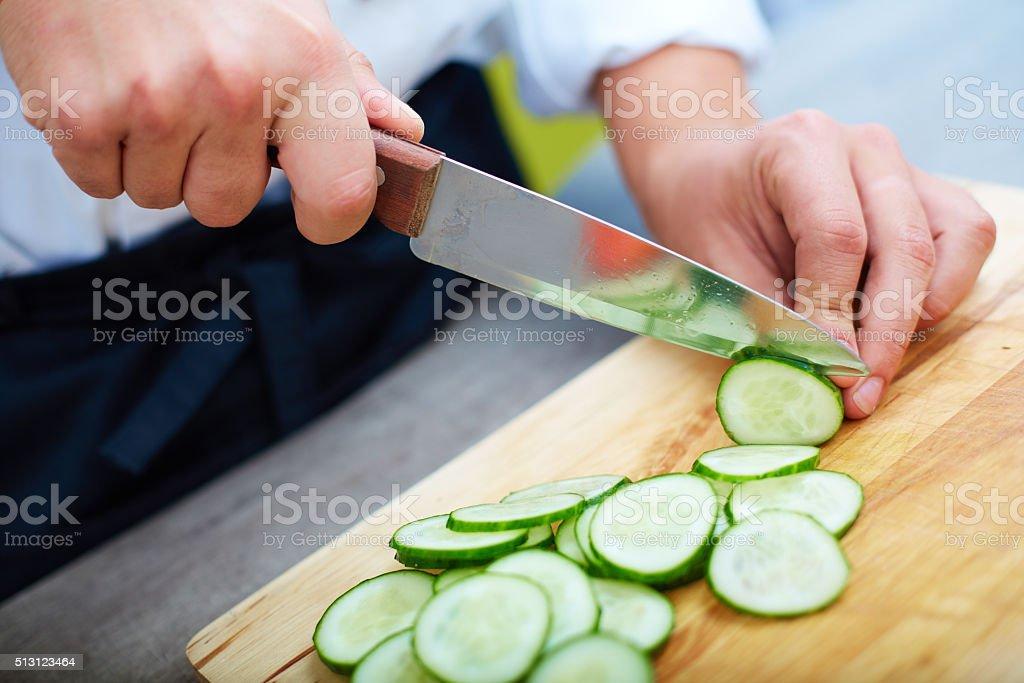 Slicing cucumbers stock photo