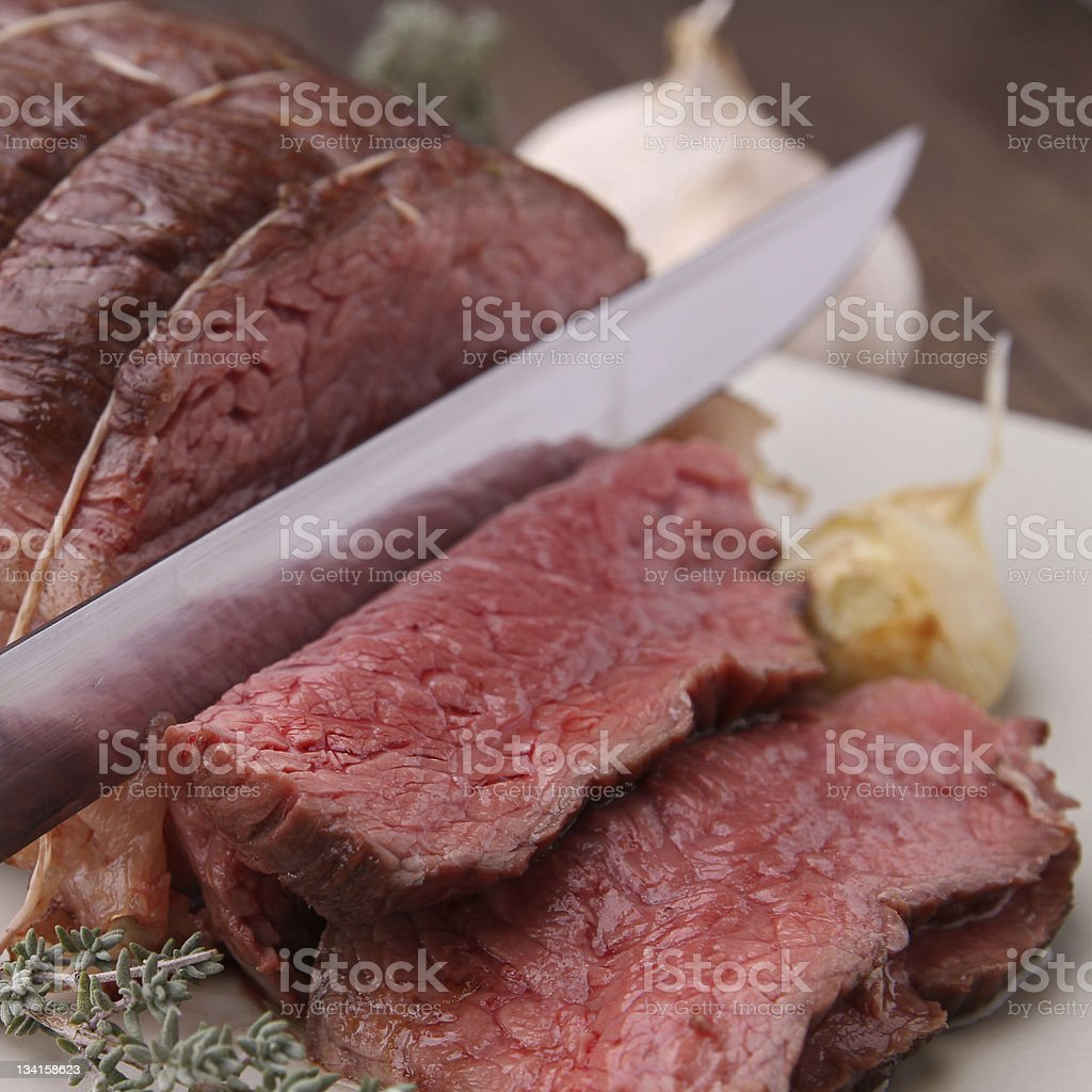 Slicing of a medium rare roast beef stock photo