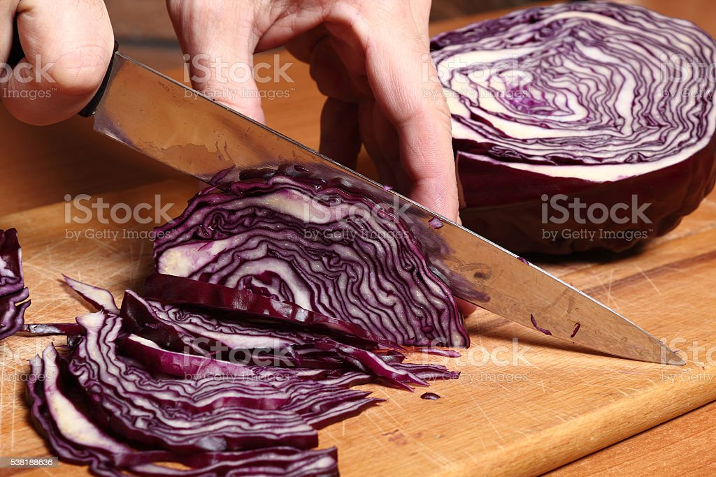 Slicing red purple cabbage stock photo
