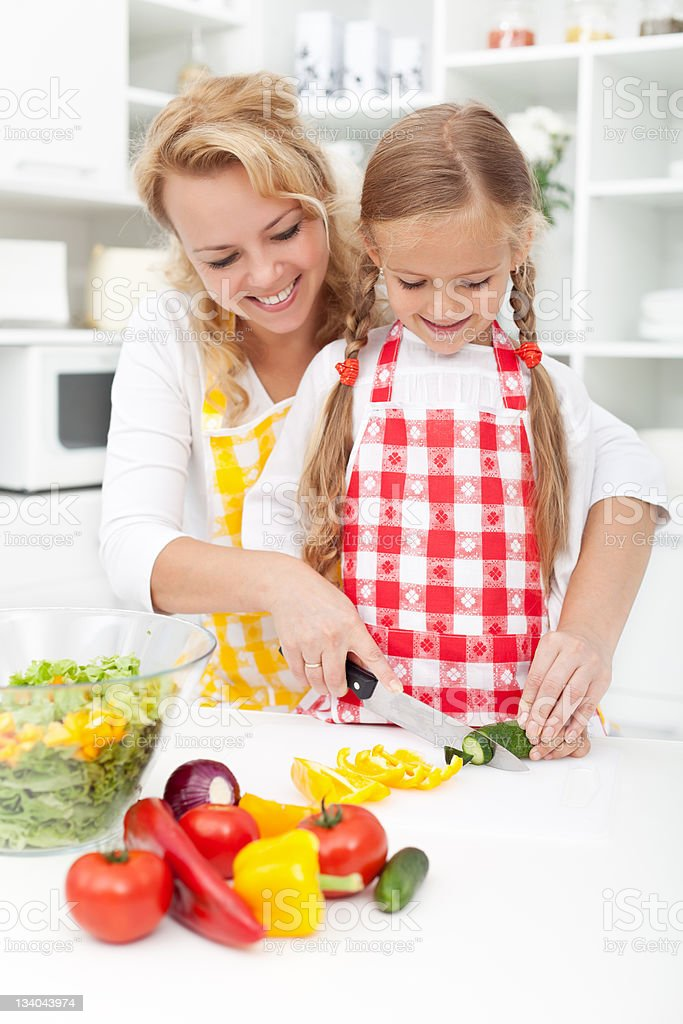 Slicing vegetables in kitchen royalty-free stock photo