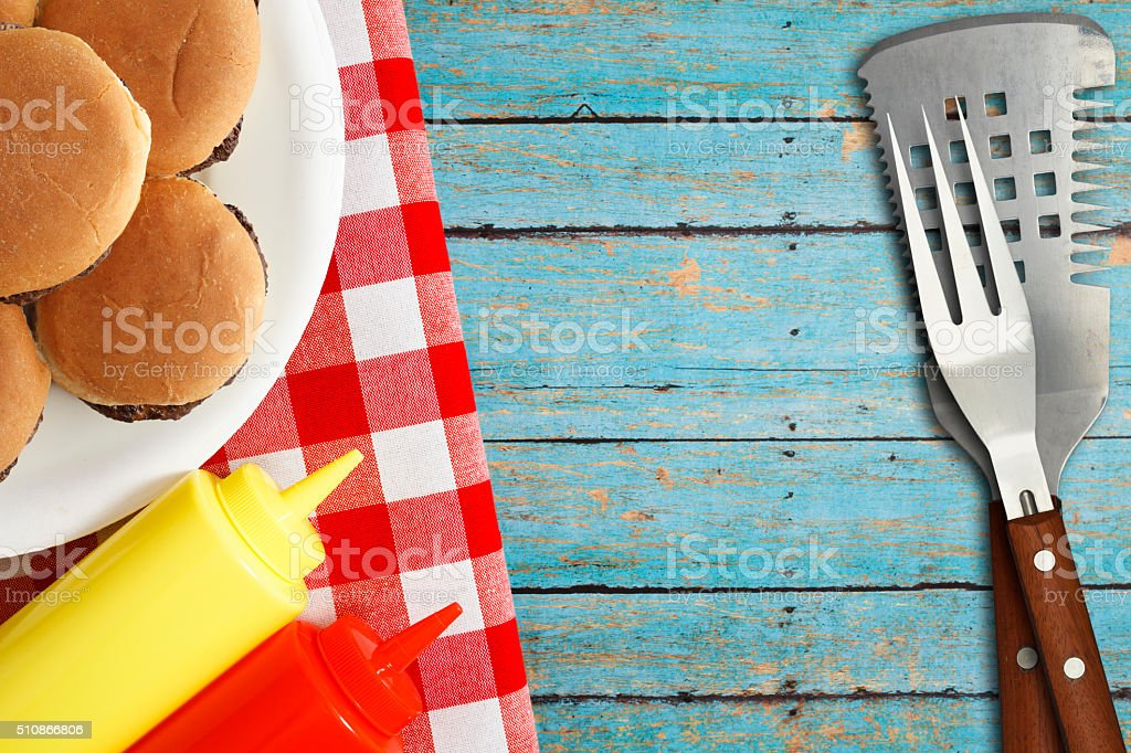 Slider Burgers with Condiments and Grilling Utensils stock photo