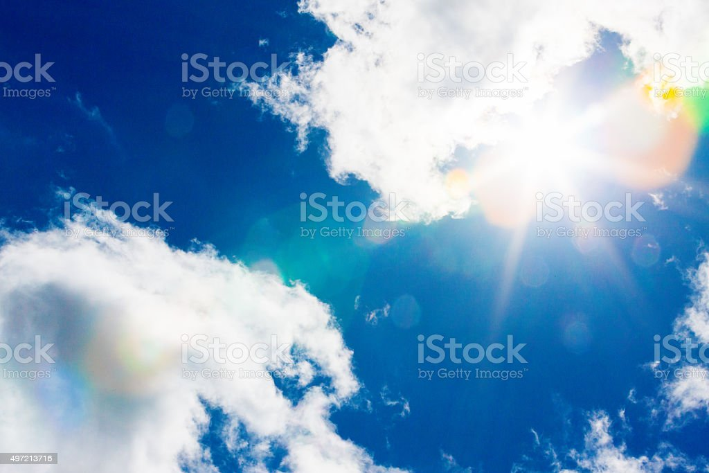 Slightly clouded sky with radiating rainbow flare from sun stock photo