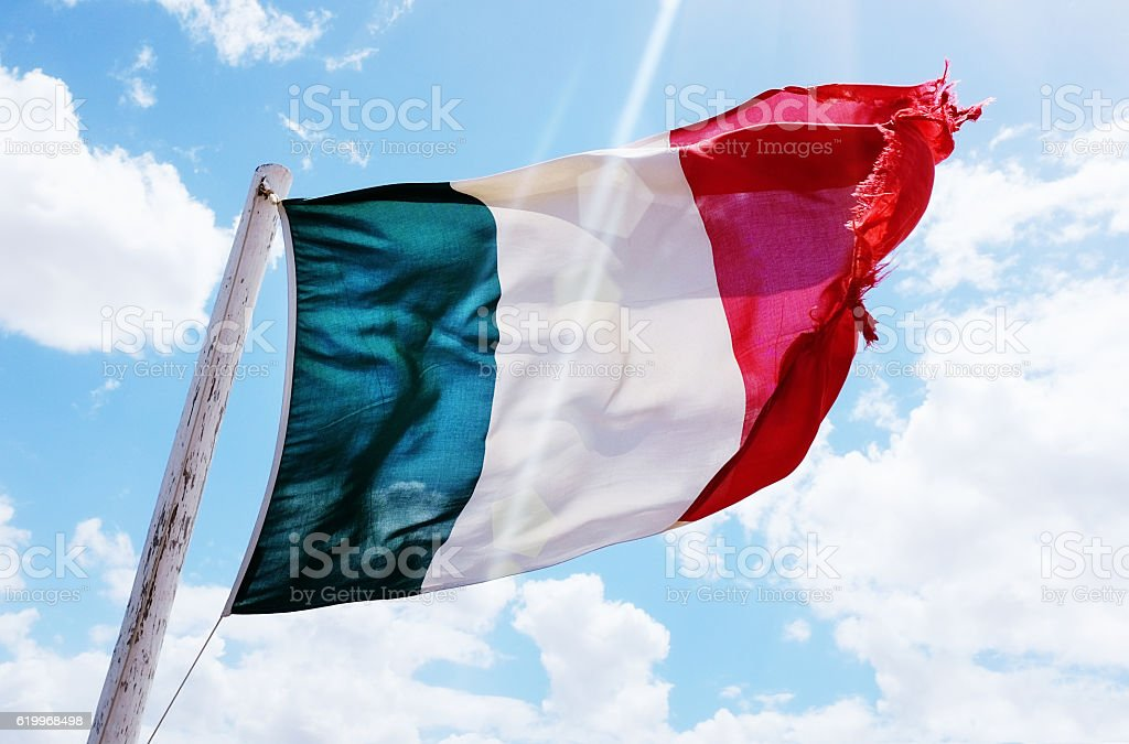 Slightly frayed Italian national flag blowing in the breeze stock photo