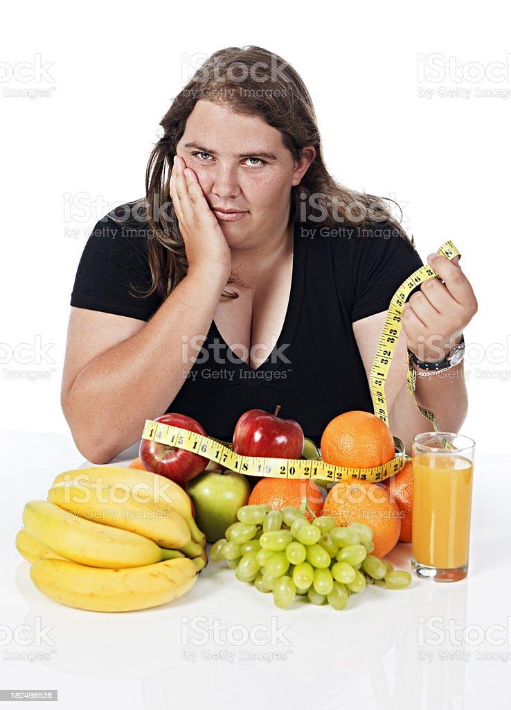 Slightly glum chubby woman considers tape measure and fruit stock photo