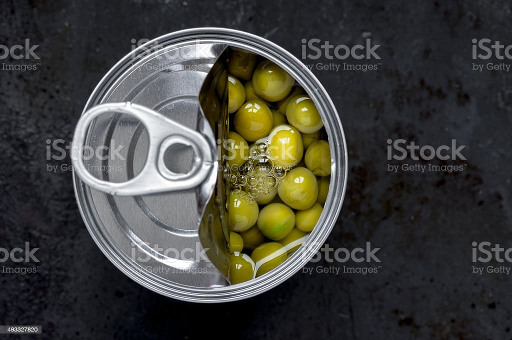 Slightly open tin of green peas stock photo
