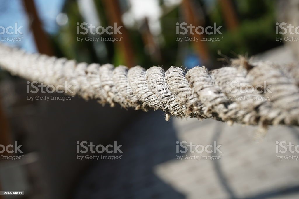 Slightly used frayed thick rope made of twisted beige strings stock photo