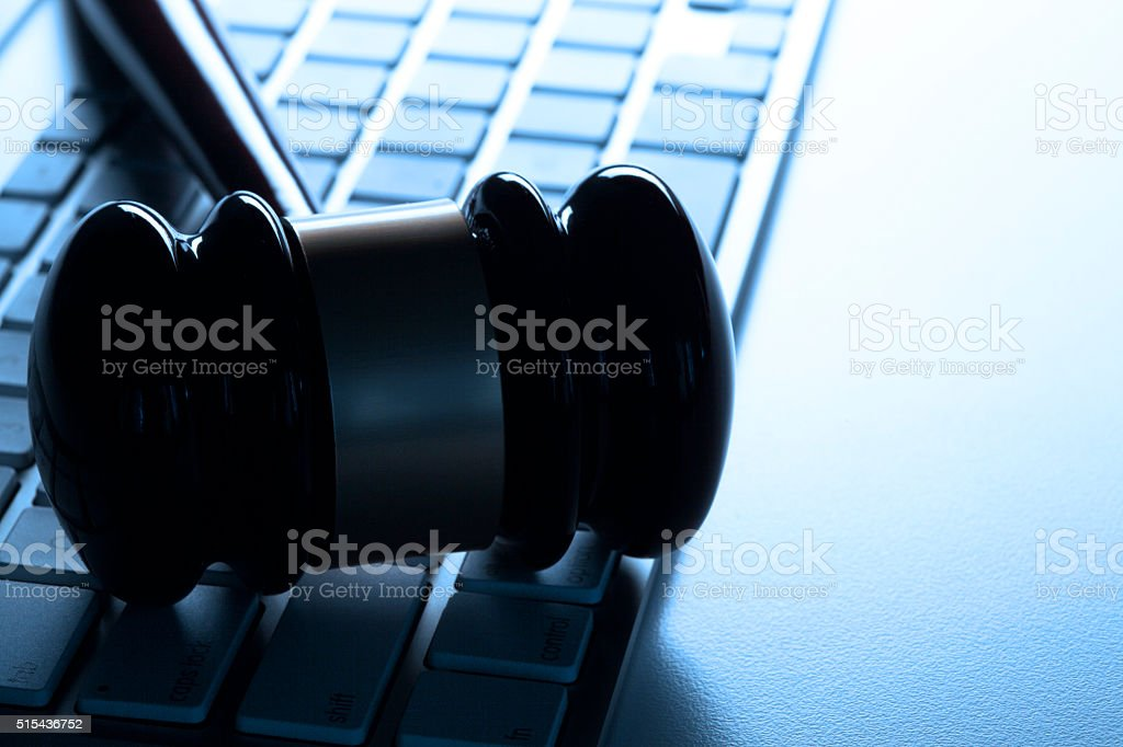 Slihouetted Gavel Resting On A Computer Keyboard stock photo