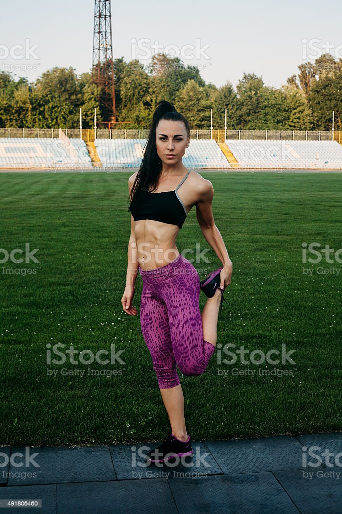 Slim athletic woman with dumbbells in the stadium stock photo