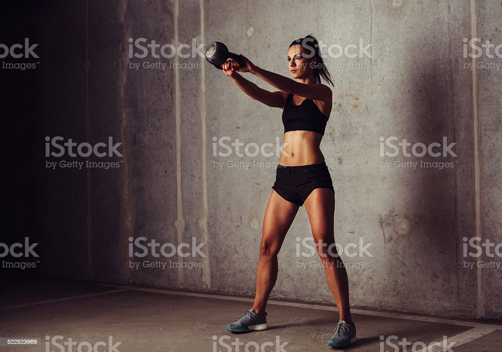 Slim attractive sportswoman in a kettlebell training stock photo