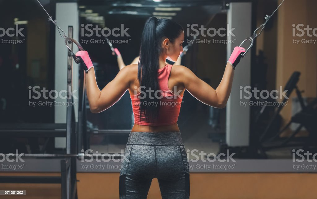 Slim, bodybuilder girl, does the exercises standing in front of the mirror in the gym. stock photo