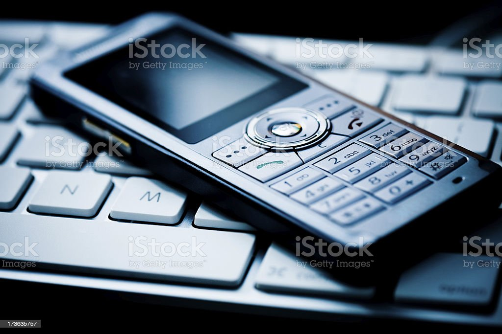 slim cell phone on keyboard royalty-free stock photo