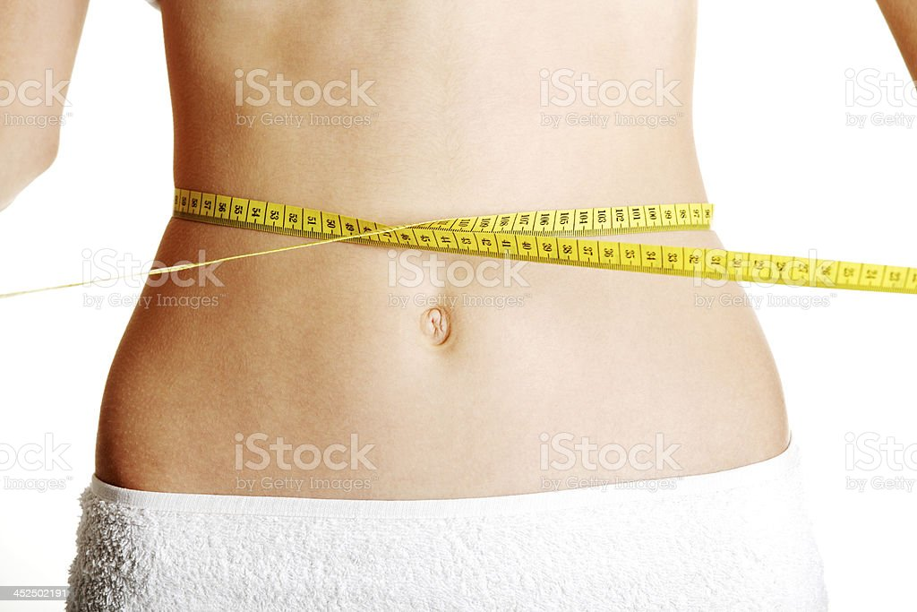 Slim fit flat belly with measuring tape. royalty-free stock photo