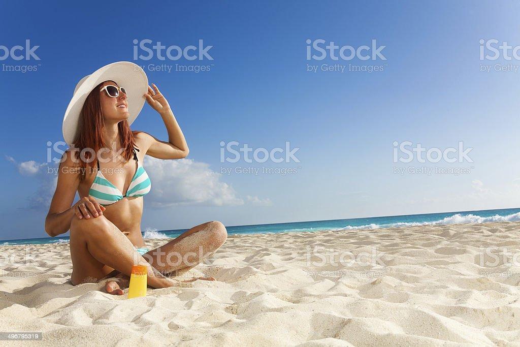 Slim girl in blue striped bikini on seashore stock photo