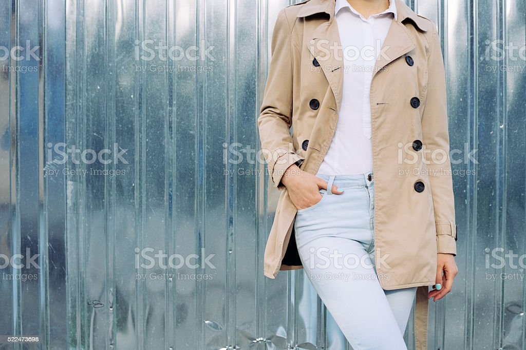 Slim girl in jeans, a beige coat and shirt outdoors stock photo