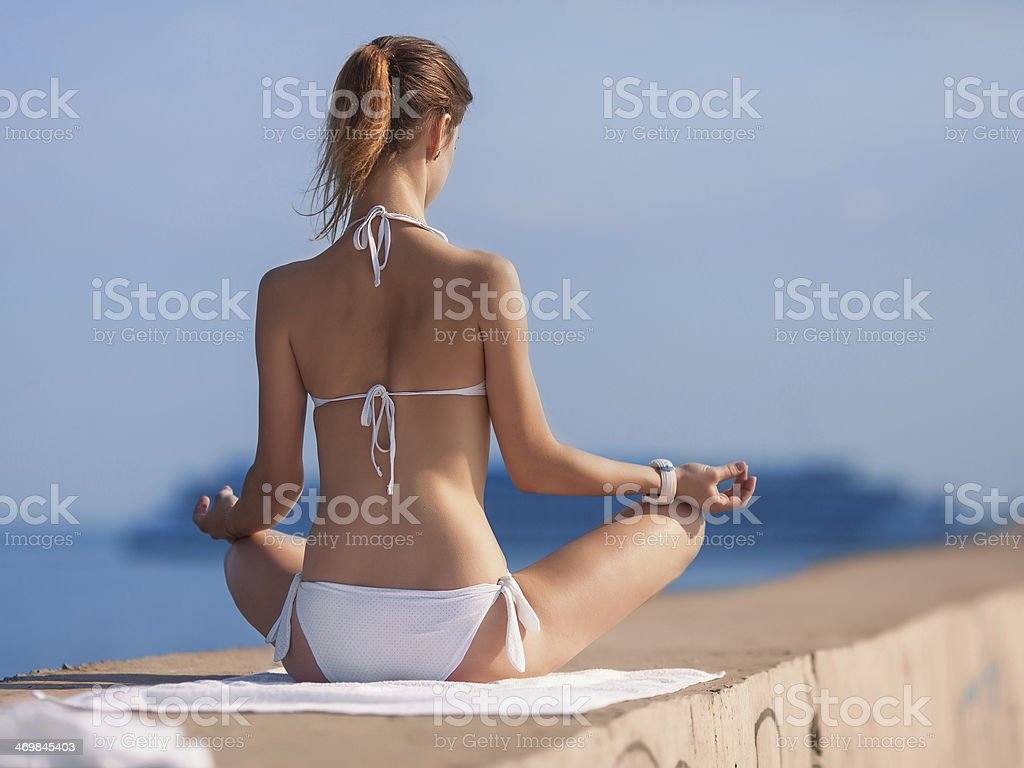 Slim girl sitting on pier observing cruise liner royalty-free stock photo
