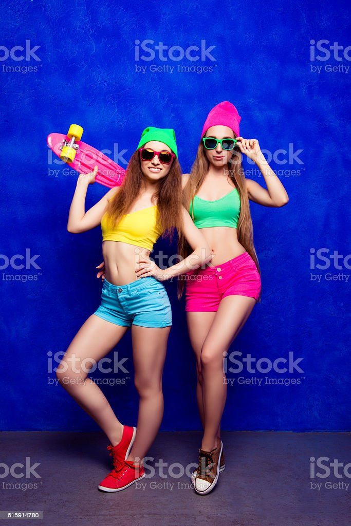 Slim hipster woman in glasses and hats holding skateboard stock photo