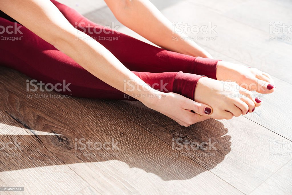 Slim legs of young woman gymnast sitting and stretching stock photo
