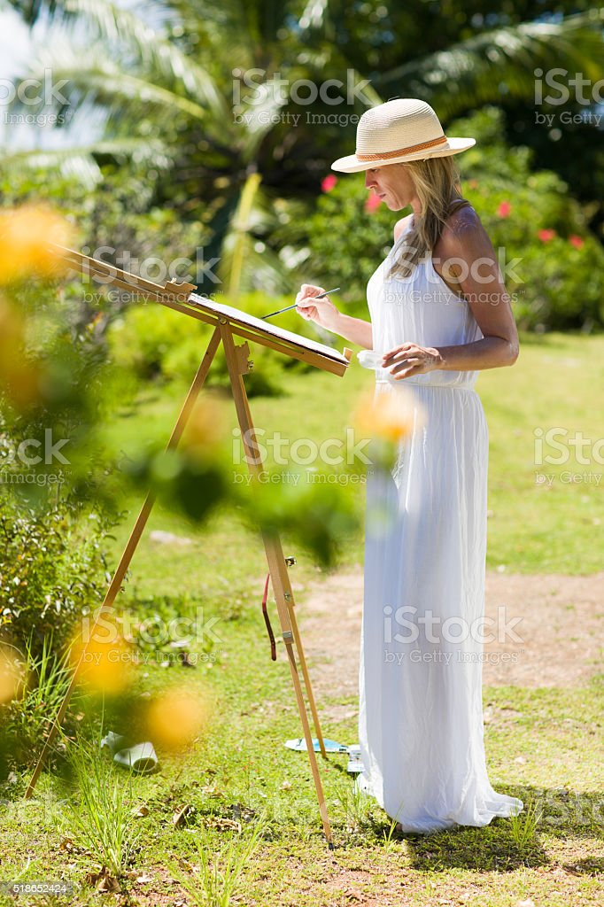 Slim painter woman, white dress and hat in tropical environment stock photo