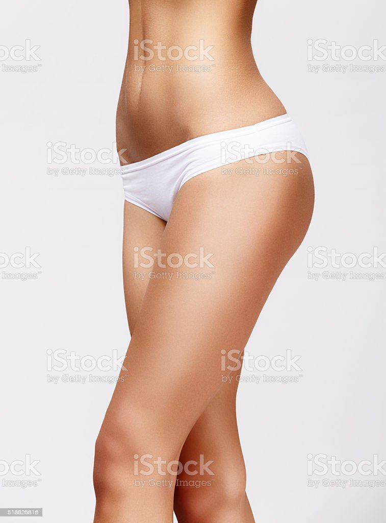 Slim tanned woman's body over gray background stock photo