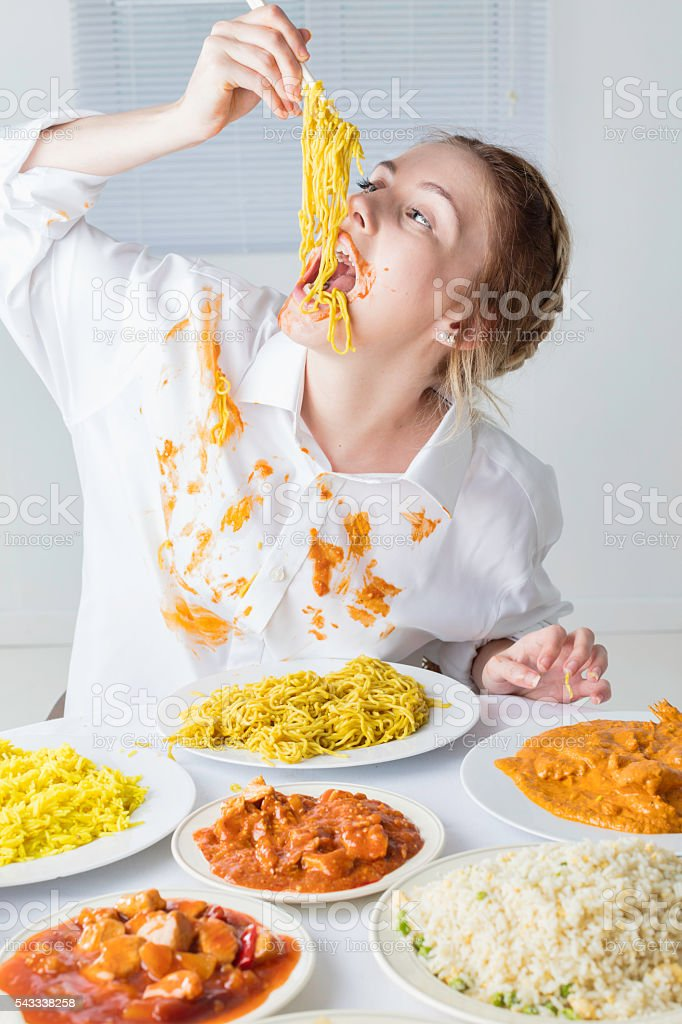 Slim Teenage Glutton Eating A Massive Meal stock photo