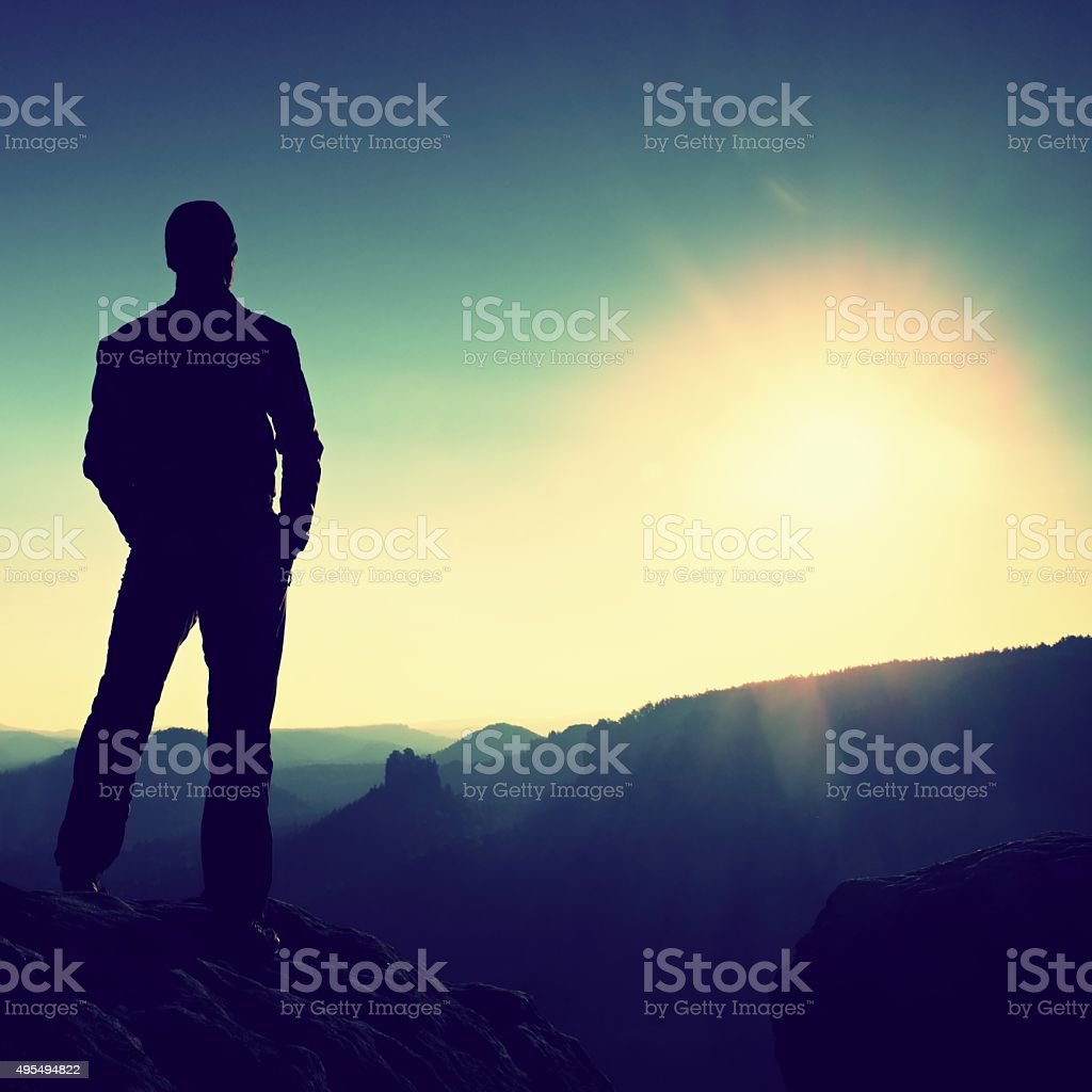 Slim tourist on mountain watch over morning valley to Sun stock photo